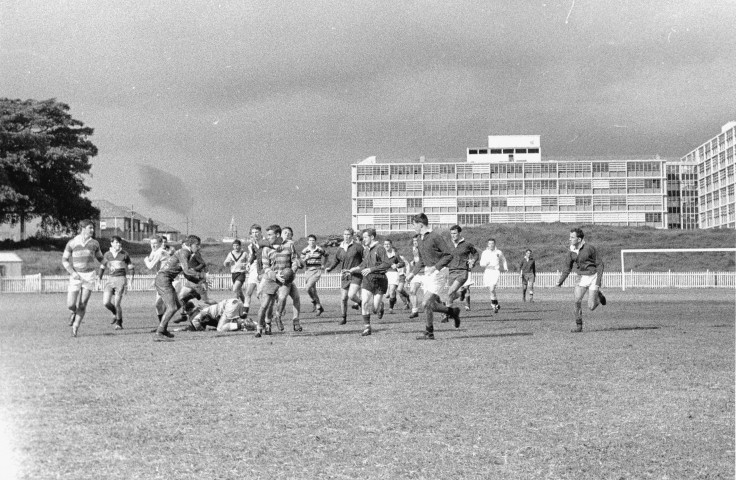 A game of rugby between Medicine II and Medicine III played on Randwick Oval with the Wallace Wurth School of Medicine and School of Biological Sciences Building in the background, 1963. (Photographer: D. Smith, UNSW Archives CN944/194)